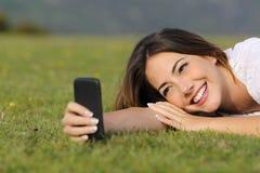 微笑使用一个巧妙的电话的俏丽的女孩说谎在草 库存图片