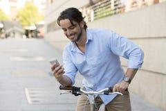 微笑使用在葡萄酒凉快的减速火箭的自行车的手机的年轻愉快的人 图库摄影