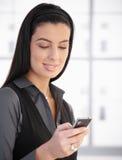 微笑使用妇女的移动电话 免版税库存照片