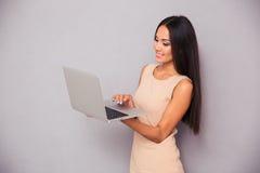 微笑使用妇女的膝上型计算机纵向 库存图片