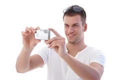 微笑使用年轻人的照相机数字式人 免版税库存照片