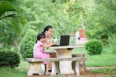 微笑使用膝上型计算机的两个姐妹室外 免版税库存照片