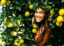 微笑俏丽的回教的妇女在橙色树丛里,真正的回教女孩che 免版税库存图片