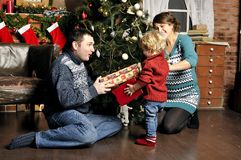微笑做父母在家给圣诞节礼物儿子 免版税图库摄影