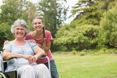 微笑入凸轮的轮椅和孙女的祖母 库存照片