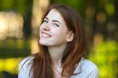 微笑入照相机室外模糊的森林公园背景的一名年轻红头发人妇女的画象 免版税库存照片