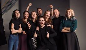 微笑八个年轻的朋友一起站立,拥抱,笑和 在灰色墙壁射击的演播室 图库摄影