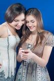 微笑兴奋的电话二个妇女年轻人 免版税图库摄影