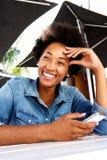 微笑凉快的年轻非洲的妇女和固定的单元电话 库存图片