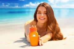 微笑华美的妇女的画象,当放松在海滩和拿着遮光剂瓶时 免版税库存图片