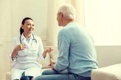 微笑友好的医生,当咨询退休的绅士时 免版税库存图片