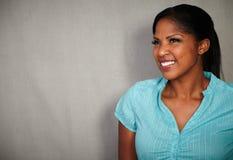 微笑反对灰色背景的愉快的妇女 免版税库存图片