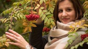 微笑反对秋天叶子背景的一名可爱的白种人妇女的画象  免版税库存照片