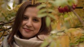 微笑反对秋天叶子背景的一名可爱的白种人妇女的画象  免版税库存图片