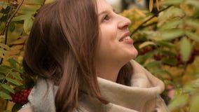 微笑反对秋天叶子背景的一名可爱的白种人妇女的画象  库存图片