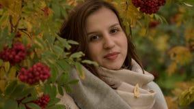微笑反对秋天叶子背景的一名可爱的白种人妇女的画象  免版税图库摄影