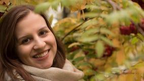 微笑反对秋天叶子背景的一名可爱的白种人妇女的画象  库存照片