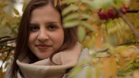 微笑反对秋天叶子背景的一名可爱的白种人妇女的画象  图库摄影