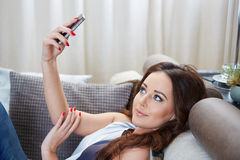 微笑可爱的妇女,她读sms 库存图片