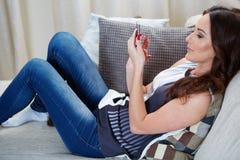 微笑可爱的妇女,她读sms 免版税图库摄影