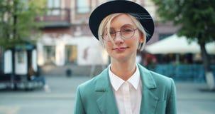 微笑可爱的学生的金发碧眼的女人画象帽子和玻璃的户外 股票录像