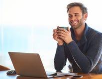 微笑可爱的年轻的人,当拿着咖啡杯时 免版税库存图片
