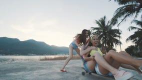 微笑和乘坐在海滩的longboard的三个朋友妇女在日落 股票视频
