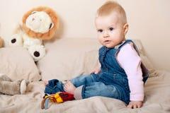 微笑和使用与玩具的可爱的女婴 免版税库存图片