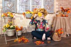 微笑和使用与秋叶的愉快的妇女 秋天美丽的日秋天森林走的妇女 库存图片