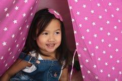 微笑和使用在桃红色帐篷的亚裔小孩 免版税库存图片