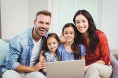 微笑和使用在沙发的家庭画象膝上型计算机 库存照片