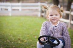 微笑和使用在玩具拖拉机的微笑的年轻小孩外面 库存图片
