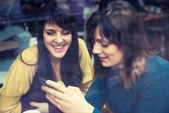 微笑和使用巧妙的电话的两个女孩在咖啡馆 免版税库存图片