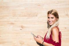 微笑和使用手机室外po的美丽的白肤金发的妇女 免版税库存照片
