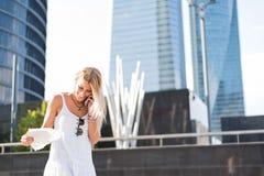 微笑和使用手机室外po的美丽的白肤金发的妇女 库存照片