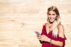微笑和使用手机室外po的美丽的白肤金发的妇女 免版税库存图片
