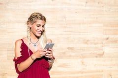 微笑和使用手机室外po的美丽的白肤金发的妇女 库存图片