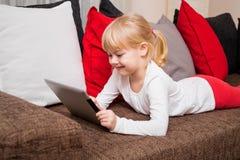 微笑和使用片剂的小女孩 免版税库存照片