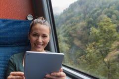 微笑和使用片剂的年轻女人为学习,当旅行乘火车时 免版税图库摄影