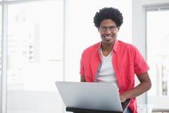 微笑和使用膝上型计算机的偶然商人 库存图片