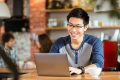 微笑和使用膝上型计算机的愉快的快乐的亚洲男性在咖啡馆 库存照片