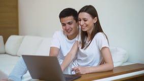 微笑和使用膝上型计算机的逗人喜爱的年轻夫妇在长沙发在明亮的客厅 影视素材