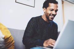 微笑和使用膝上型计算机的年轻非洲人,当坐在他的现代coworking的地方时 愉快的商人的概念 库存照片