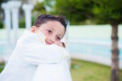 微笑和倾斜在白色的年轻人第一个圣餐男孩木 图库摄影