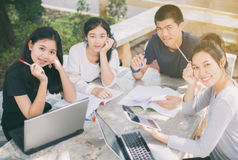 微笑和分享有w的想法的亚洲小组学生 库存图片