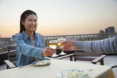 微笑和吃在屋顶上面的年轻夫妇,敬酒 库存照片