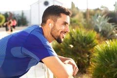 微笑和听到与耳机的音乐的适合的年轻人 库存照片