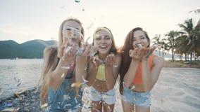 微笑和吹在海滩的三个朋友妇女五颜六色的闪烁在日落 股票视频
