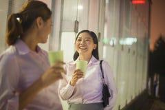 微笑和喝咖啡的年轻女实业家户外在晚上 免版税库存照片