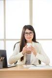 微笑和喝在膝上型计算机的愉快的亚裔女商人咖啡 免版税库存图片